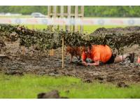 Runner and dog army crawl through mud.