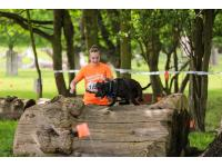 Runner and dog take on the log obstacle.