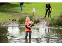 Runner carries dog through lake obstacle.